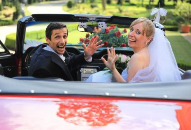 Young wedding couple waving in cabriolet car