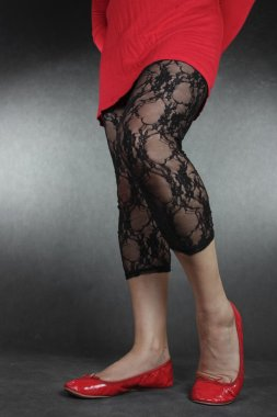 Woman legs wearing black lace leggins and red dress over grey ba