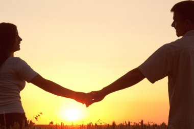 Young couple holding hands and looking at each other on sunny summer day