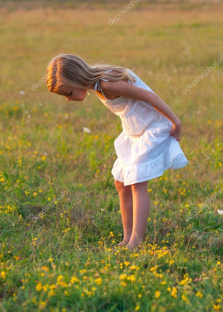 Cute little girl in white dress exploring the meadow on sunny spring day