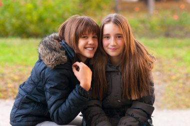 Two happy teenage girls having fun in the park on beautiful autumn day