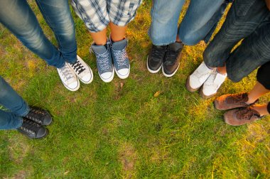 Legs and sneakers of teenage boys and girls standing in half circle on the grass