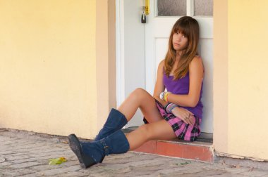 Cute sad teenage girl sitting in front of the white door