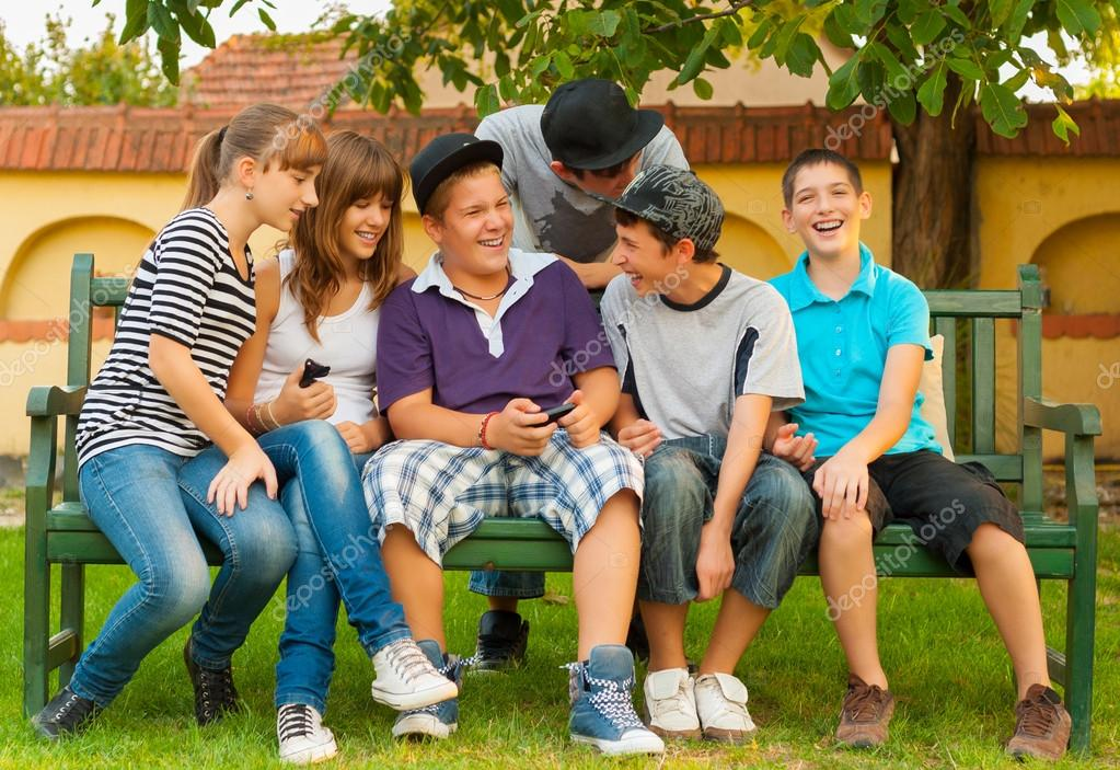 Teenage boys and girls having fun in the garden while sitting on the bench