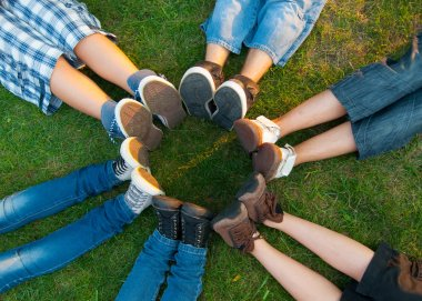Teenage friends forming circle with their legs