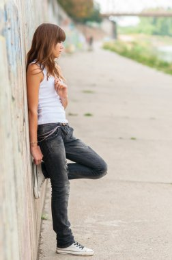 Lonely teenage girl leaning against concrete wall in urban environment