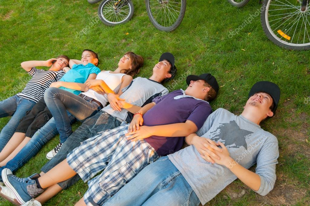Teenage boys and girls lying on the grass after riding bicycles