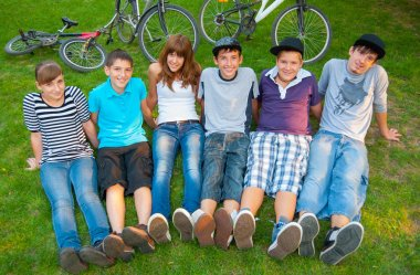 Happy teenage boys and girls resting in the grass after riding bicycles