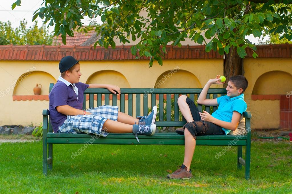 Two teenage boys sitting on the bench and throwing ball to each other
