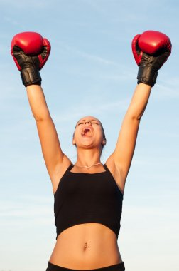 Victorious sports woman in red gloves against blue sky on sunny summer day.