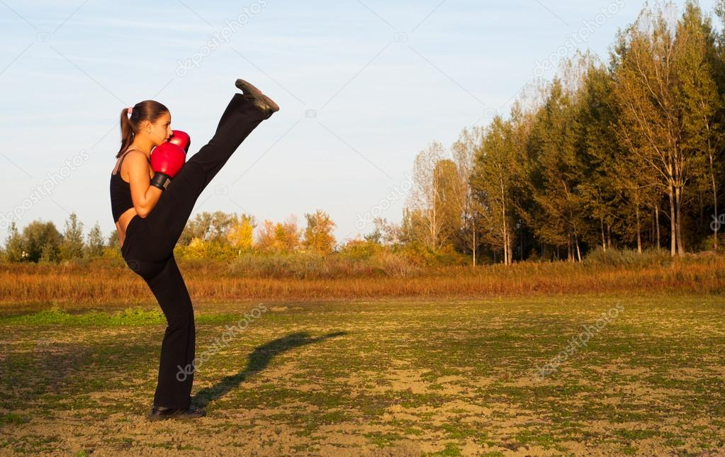Beautiful kick boxing girl exercising high kick in the nature on sunny summer day.