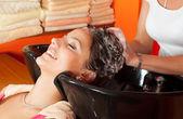 szép fiatal lány élvezi a hajmosás, fodrászat