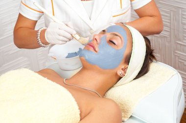 Beautiful young woman lying on massage table while facial mask is put on her face