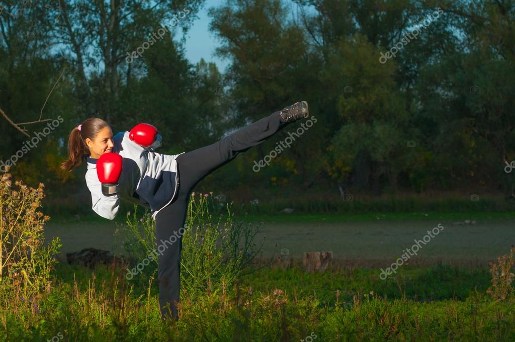Beautiful kickboxing girl exercising high kick in the nature at night