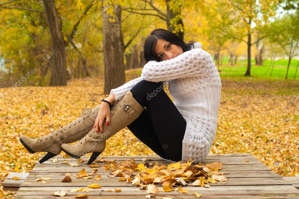 Beautiful lady sitting on the table in the park on cloudy autumn day