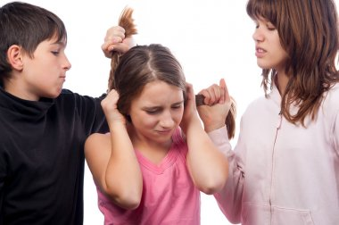 Teenage boy and teenage girl pulling hair of smaller teenage girl