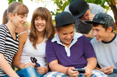 Teenage boys and girls having fun outdoor on beautiful spring day