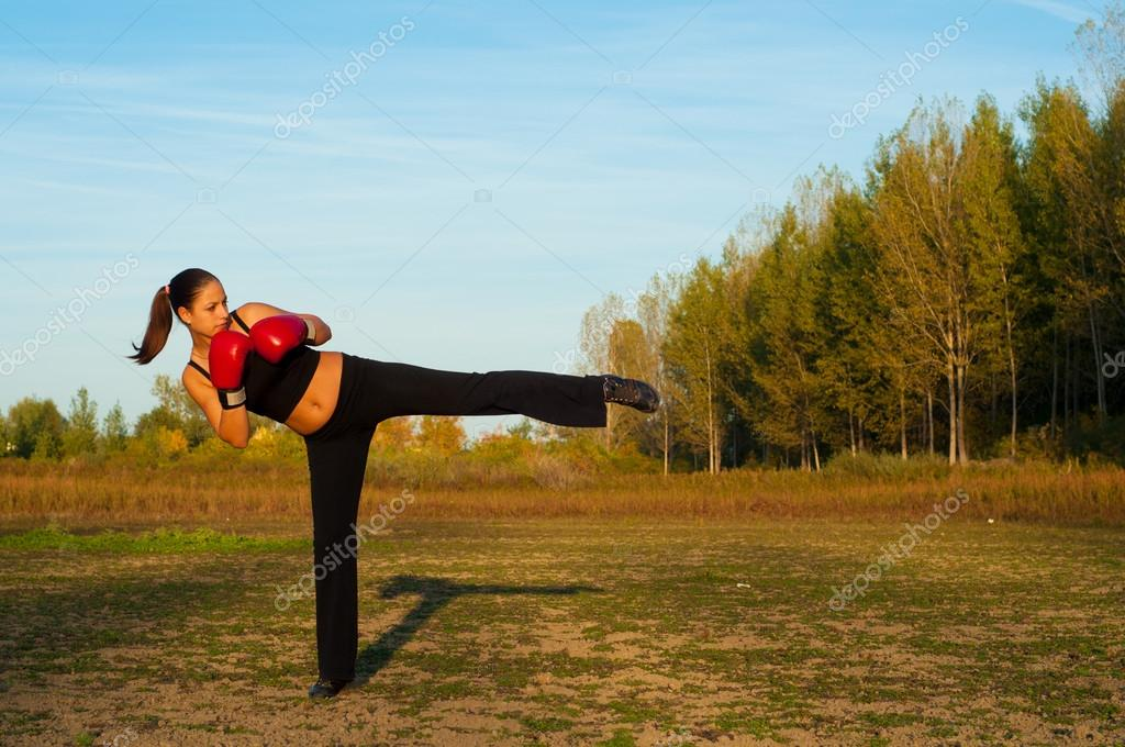 Beautiful kick boxing girl exercising kick in the nature on sunny summer day.