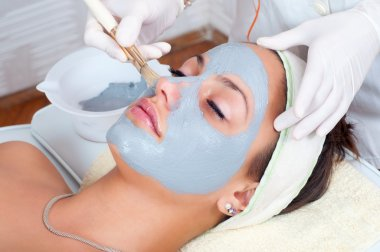 Beautiful young woman lying on massage table while facial mask is put on her face.