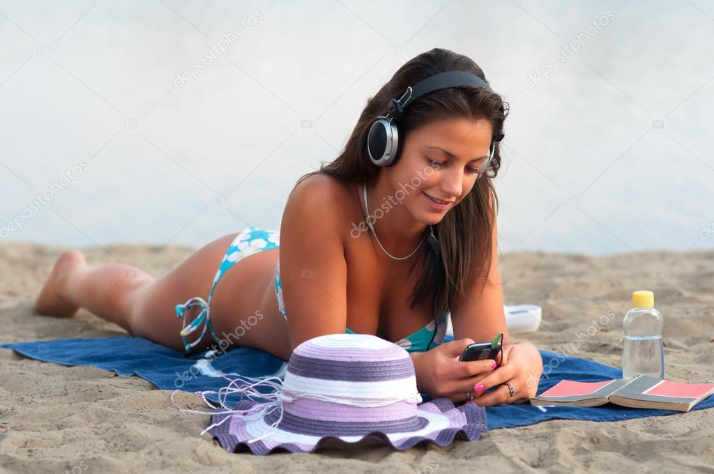 Beautiful sexy girl lying on the sandy beach at summer and listens to music