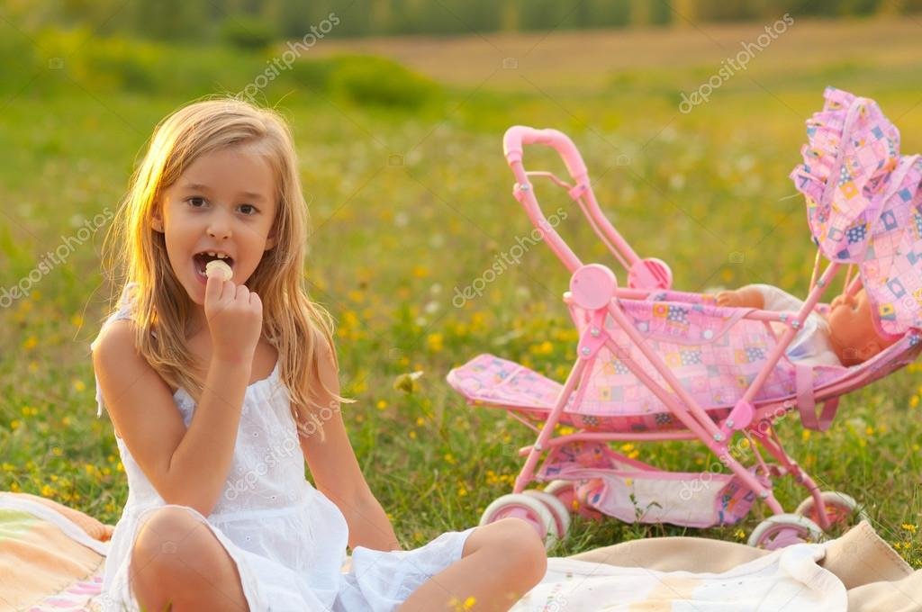 Cute little girl eating snacks while sitting on the meadow on beautiful spring day