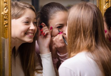 Beautiful teenage girlfriends having fun while putting make up in front of the old mirror