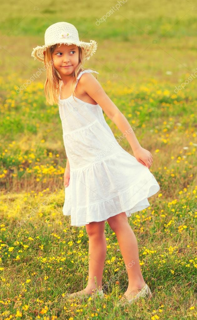 Little girl in white dress walking on the meadow