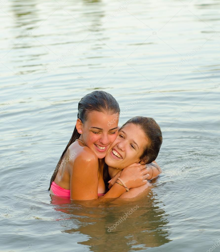 Two teenage girls hugging in the river