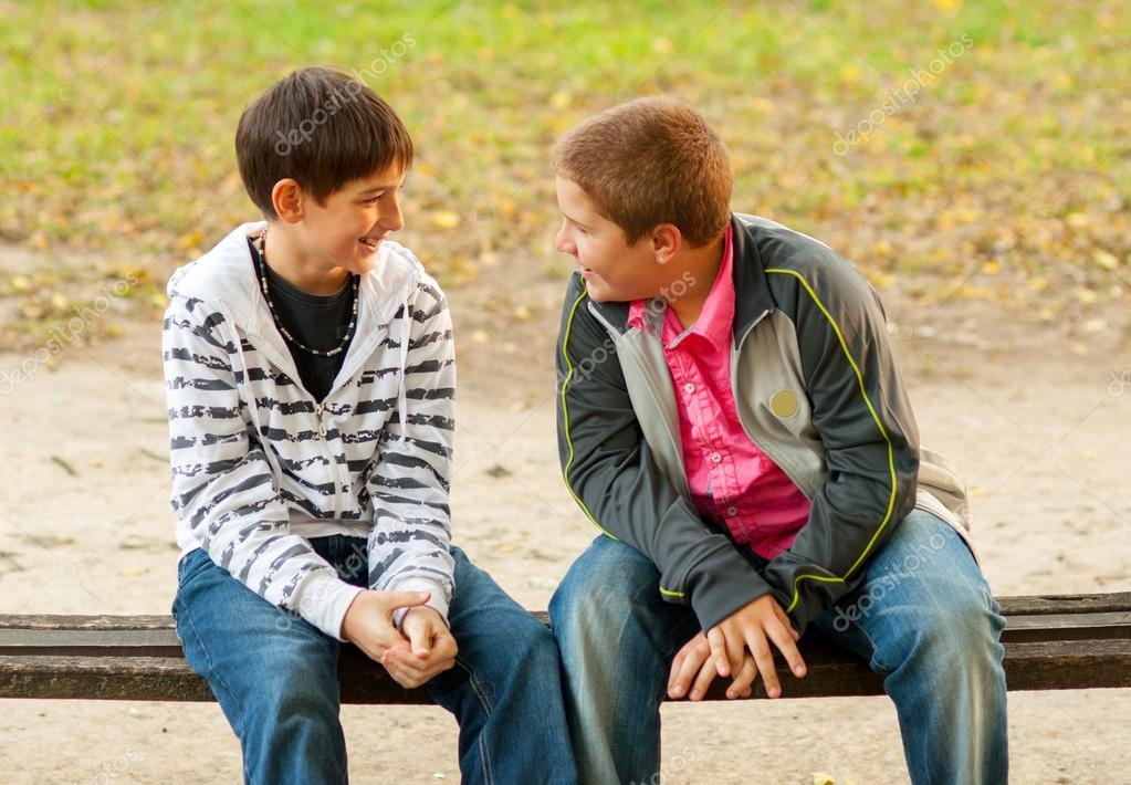Two teenage friends talking in the park