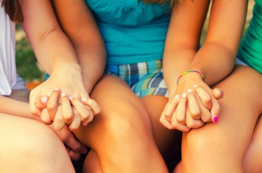 Teenage girls holding hands