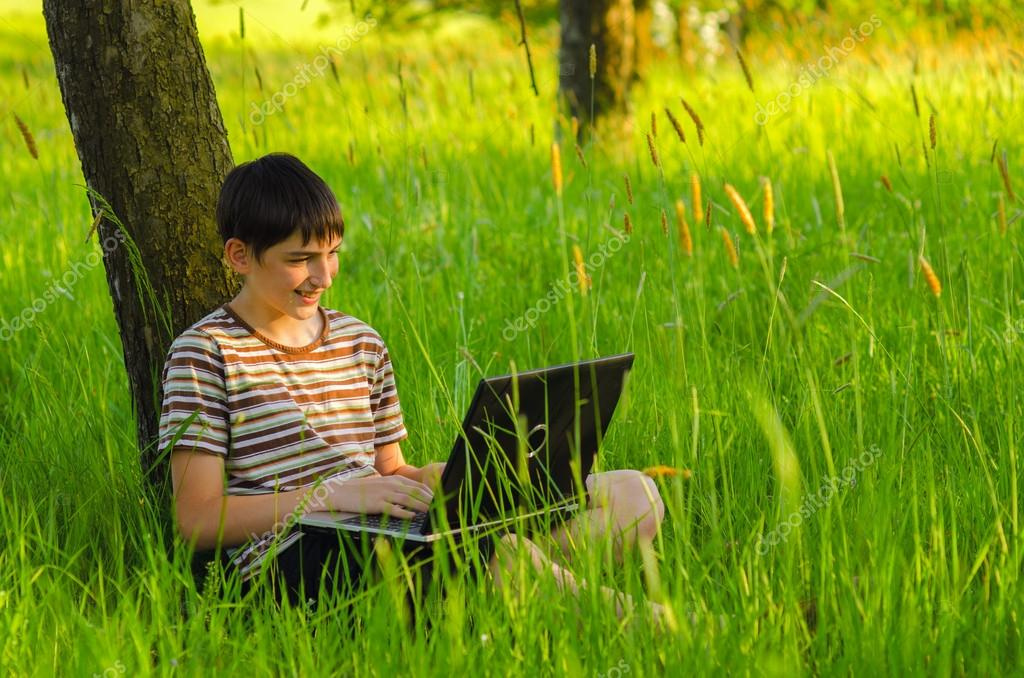 Teenage boy working on notebook in the nature