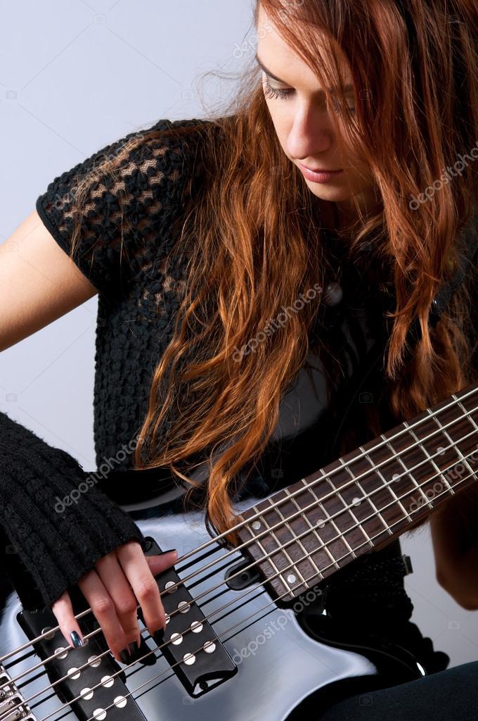 Beautiful girl playing bass guitar