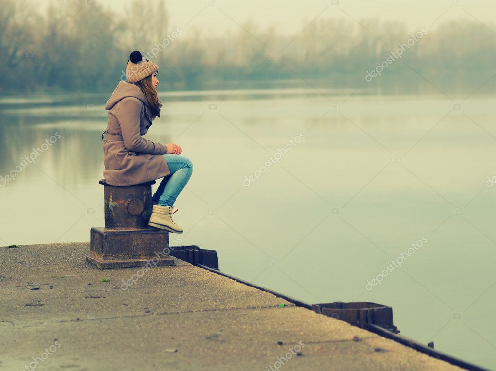 Lonely teenage girl sitting on the dock