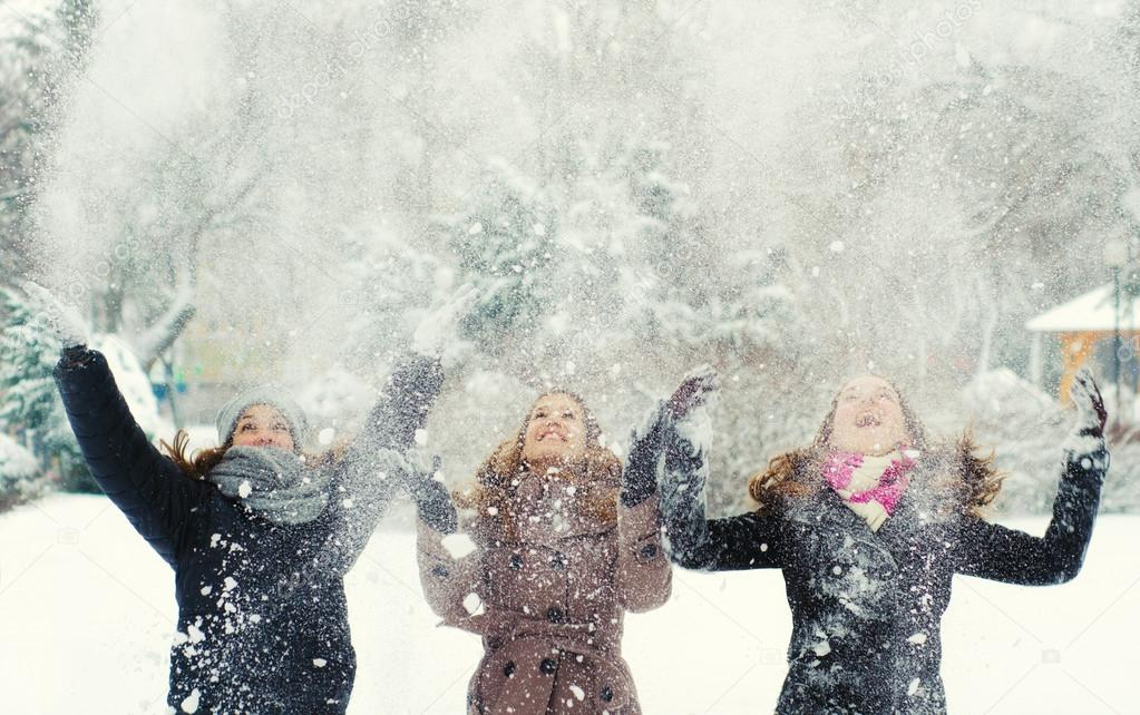 Three teenage girls throwing snow