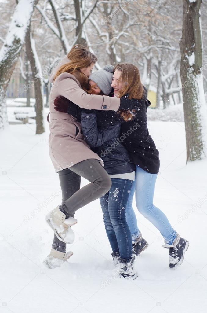 Three teenage girls playing in the snow