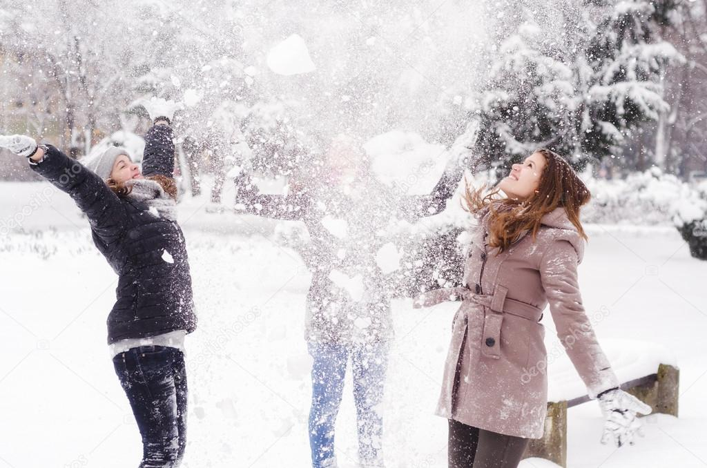 Three teenage girls throwing snow in the air