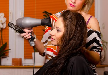 Hairdresser making hair of beautiful girl
