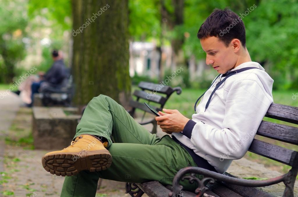 Young man working on pad device in the park
