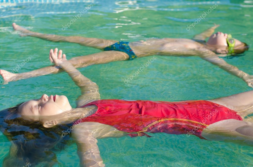 Little boy and litlle girl floating on the water surface of the