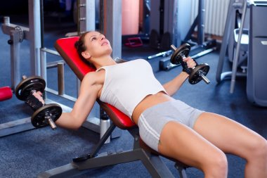 Beautiful fitness girl lifting weights in the gym