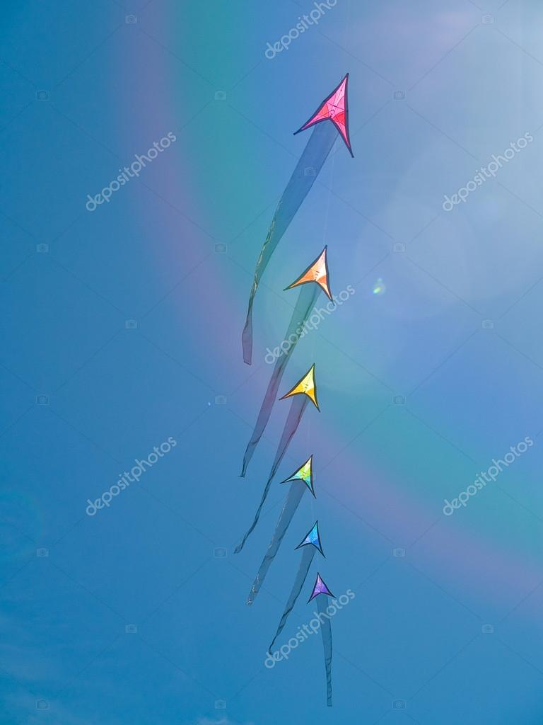 Colorful Arrow Kites Flying in a Bright Blue Sky with a Lens Flare and Rainbow
