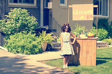Retro girl wearing sunglasses with lemonade stand