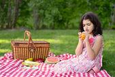 Dítě loupání pomeranče na pikniku