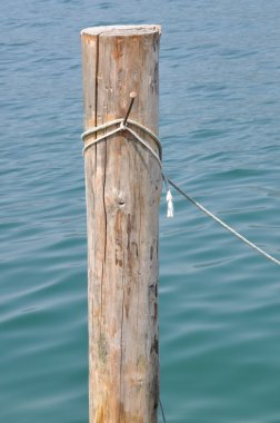 Single wooden bollard with rope