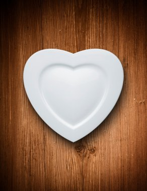 Heart form white plate on wood background