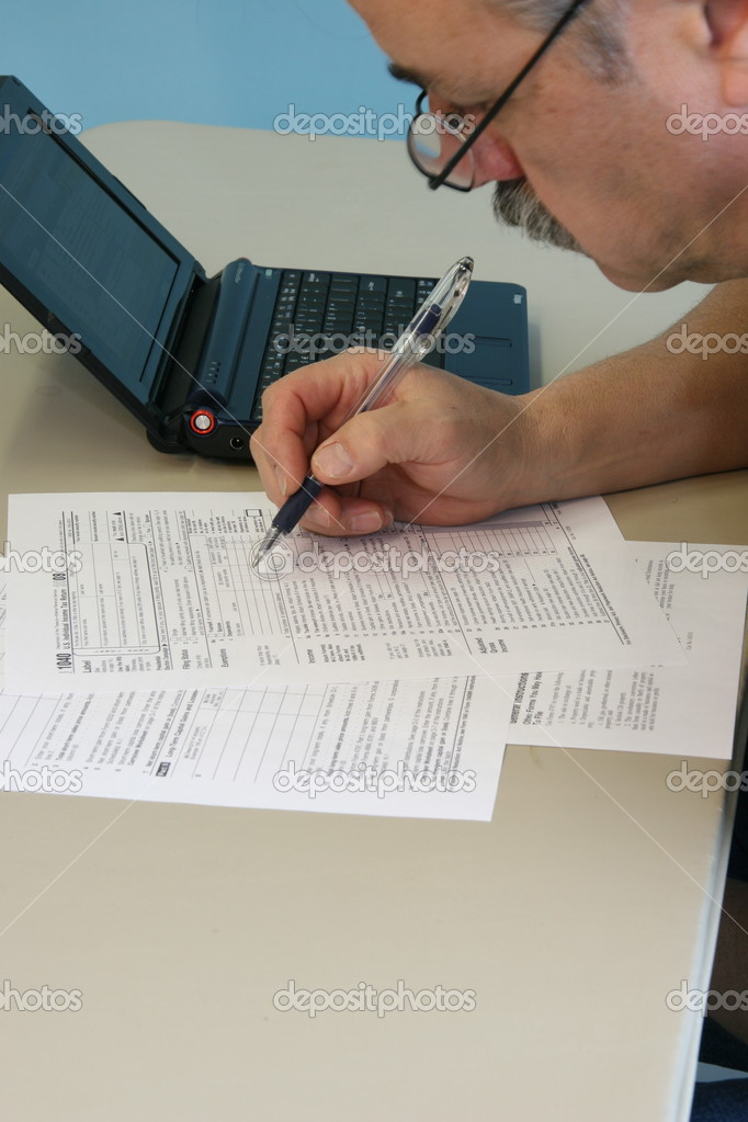 Man Filling In 1040 Federal Income Tax Form Stock Photo