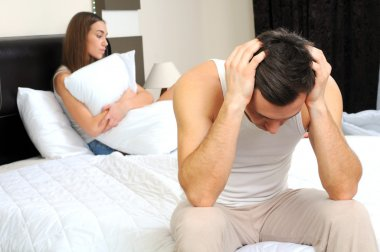Upset man having problem sitting on the bed with his girlfriend