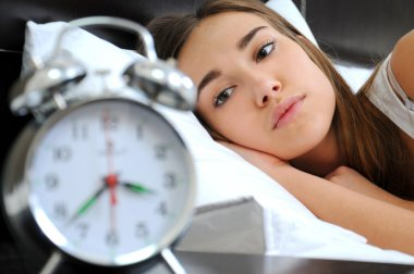 Clock with sleep at night. Woman can not sleep