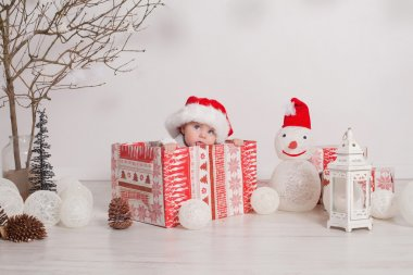 A young baby is staring at the camera wearing a Santa Christmas hat.