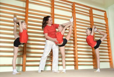 Sporty children with coach in gym